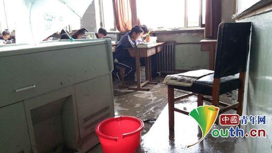 教室内地上放着桶,接屋顶漏水。