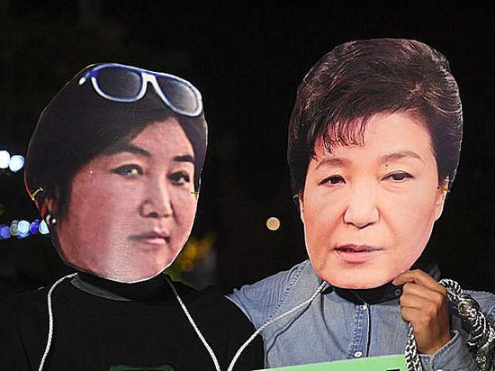 10月27日,首尔,抗议者戴着朴槿惠(右)和崔顺实的头像。(新华/法新)