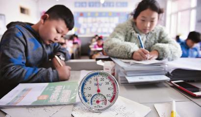 中午十一点多,这间教室温度也只有十二三度,孩子们只能穿着厚厚的衣服学习 新文化记者 郭亮 摄
