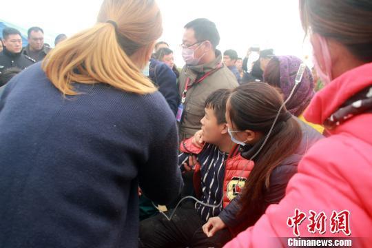 10日10时许,在河北省保定市蠡县6岁男童掉落40米深枯井救援现场,一参与井下救援人员升井后因缺氧晕倒。图为现场医护人员对晕倒志愿者(坐在中间者)实施抢救。 于俊亮 摄