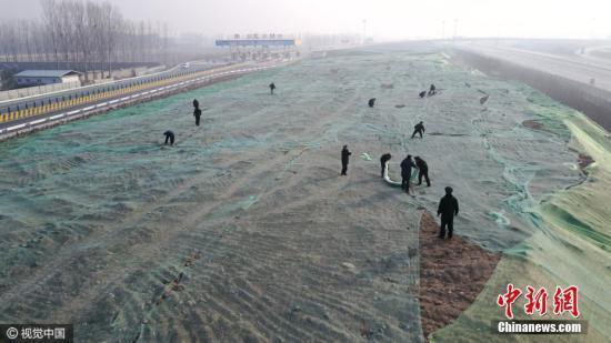 2016年12月16日,北京,大兴区安定镇京台高速安定出口处,城管队员正在苫盖建筑垃圾。图片来源:视觉中国