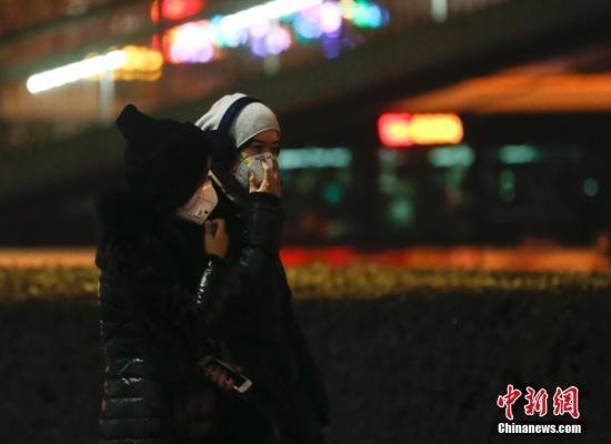 12月16日,北京民众戴防雾霾口罩出行。北京将在当日20时至21日24时启动空气重污染红色预警。中新社记者 杜洋 摄