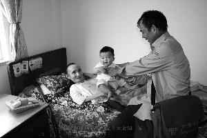 马君平在光顾光顾瘫痪在床的金士元 资料照片