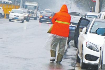 风雨中,环卫工在街头冻得瑟瑟发抖。