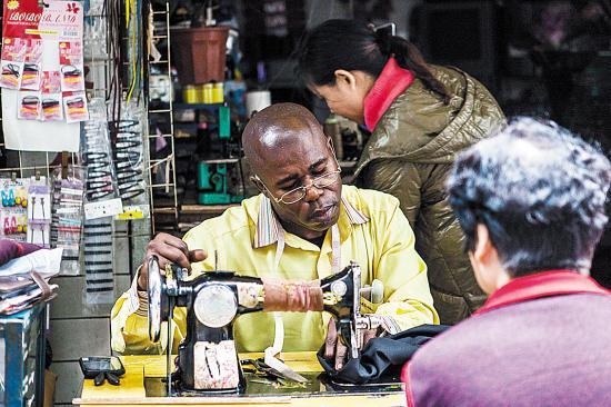 安哥拉人泰德经常借用士多老板娘的缝纫机,给采购回来的西裤修边(羊城晚报李东供图)