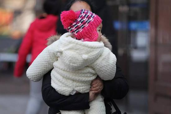 ▲2月15日,在湖南省儿童医院,一位小孩被包裹得严严实实。图|记者金林