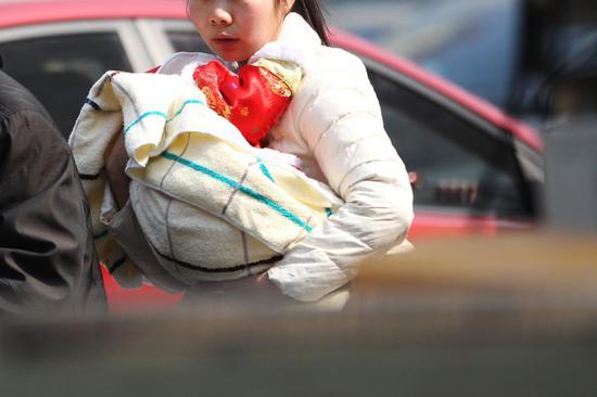 ▲2月15日,长沙今日最高温度达20℃。在湖南省儿童医院,即使天气很热,小孩仍被包裹得严严实实。图|记者金林
