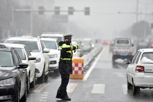 交警正在雪中指挥交通。史晟全摄