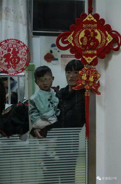 ▲2月21日晚,樊富贵的妻子抱着儿子站在病房窗前。 新京报记者 彭子洋 摄