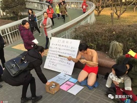 """▲2017年1月,北京地铁复兴门站出口附近,好心人在向""""打股救子""""的樊富贵捐款。 图片来源:东方IC。"""