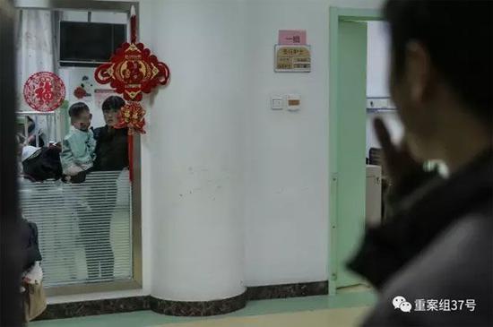 ▲2月21日晚,樊富贵的妻子抱着儿子站在病房窗前与丈夫相望。 新京报记者 彭子洋 摄