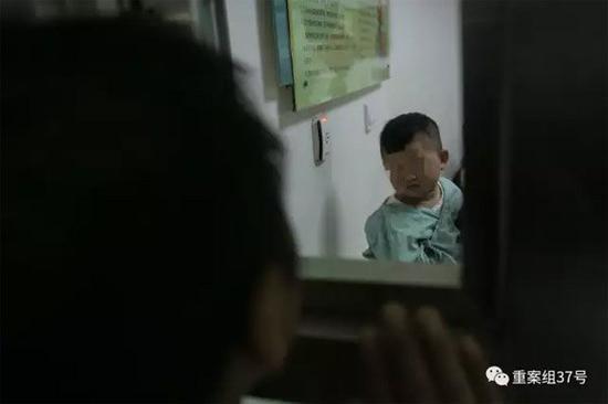 ▲2月21日晚,樊富贵与在病房里的儿子透过探视窗打招呼。 新京报记者 彭子洋 摄