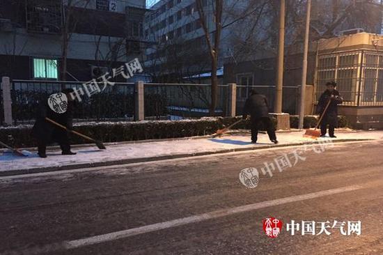 相关人员开始清理路面积雪、结冰。杨兴 摄