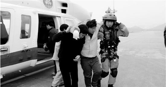 获救船员被扶下直升机。