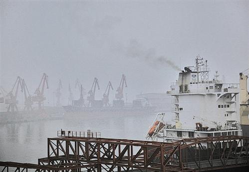 下图 2016年11月13日,天津港口码头,岸边停靠正在卸货的货轮。当日,天津各个空气监测站显示空气达到轻度甚至重度污染。一艘小型货轮即使在靠岸期间每天仍需燃烧1吨柴油以维持船上生活及工作用电。 刘飞越摄