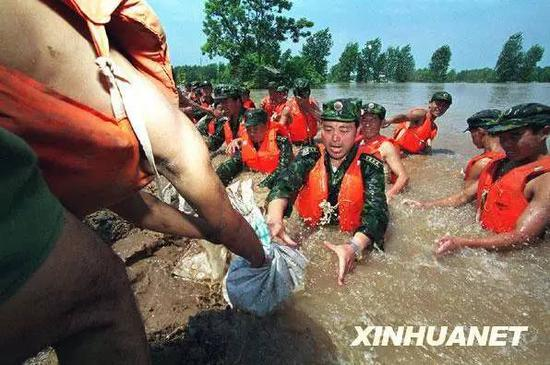 原济南军区某部官兵跳入洪水中在荆江大堤险段抢险。