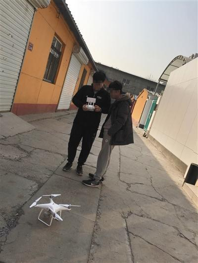 3月3日,朝阳区飞态创新店门前,一商家工作人员(左)向记者展示破解后的无人机被定位在太平洋上。