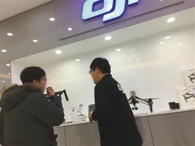 飞态创新店工作人员(右)向记者证实,该店销售的部分无人机经改装可在北京禁飞区内飞行。