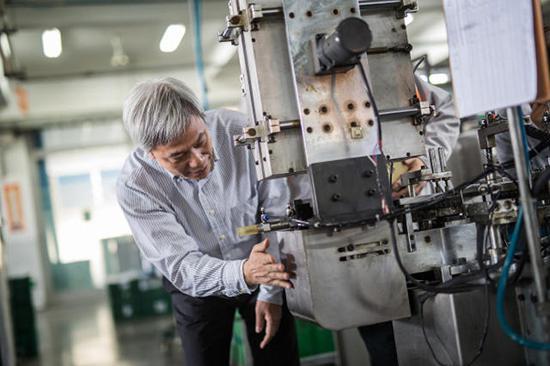 上海真彩文具股份有限公司董事长黄小喜正在调试多工位笔头加工机