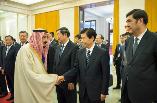 沙特国王萨勒曼与出席接待仪式的中方官员握手。