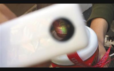 2月25日,记者拆开张建的假茅台酒检测真伪,结果显示瓶盖处有彩条(根据说明书提示,此为正品包装的特征,但记者所检测的茅台酒实际为假茅台酒)。