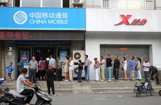 (市民排队办理为手机卡办理实名制 图片来源:视觉中国)