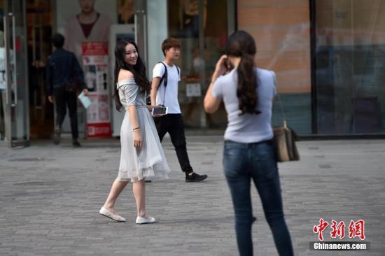 图为北京三里屯街头的姑娘小伙们换上夏装出行。 中新网记者 金硕 摄