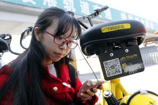 李冬雨在北京街头为被划掉多位数字的共享单车补牌。新华社记者 张玉薇/摄