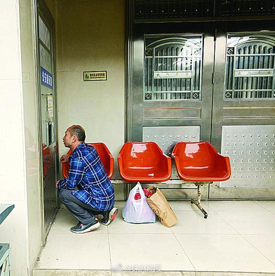 在火车站派出所的制证窗口,市民蹲着办证。