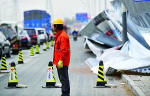 在一工地,路人从刮倒的围挡前走过。当日,北京在大风扬沙中迎来立夏,阵风可达八九级,局部地区扬沙又起。首席摄影记者 蔡代征/摄