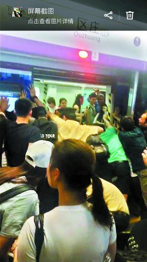 地铁工作人员和众多男乘客合力推地铁车厢。 (图片来自网友朋友圈截图,请作者与本报联系。)