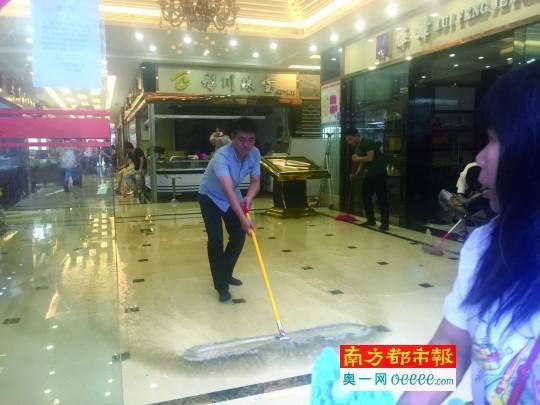 大水退去,店员正在清扫珠宝店的积水。南都记者 吴广宇摄