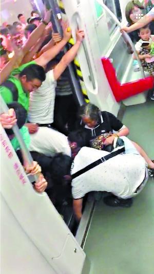 一名乘客在车厢里帮助女乘客把右腿拔出来。(图片来自网友朋友圈截图,请作者与本报联系。)