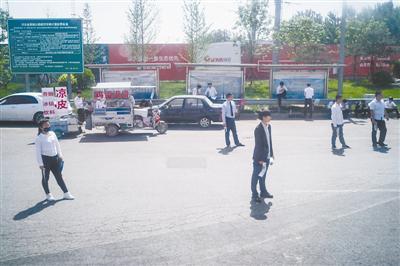 5月6日,河北固安,一些房产中介在高速路口等候购房者。