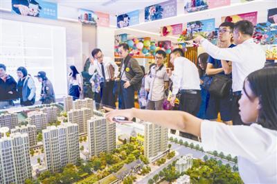 """5月6日,河北固安的一处售楼中央,来自北京的看房团正在听售楼员的解说。固安北距天安门约50公里,近年来,这里已成为不少""""北漂""""购房的新行止。"""