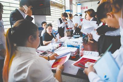5月8日,河北燕郊的房管局大厅,房产中介正在为购房者管理相关手续。今年新的购房政策出台以后,燕郊住房生意业务量有所下降。