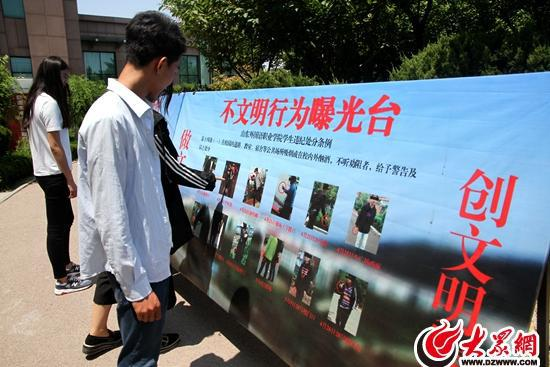 山東外國語職業學院學生在曝光台前觀看各類不文明行為照片。