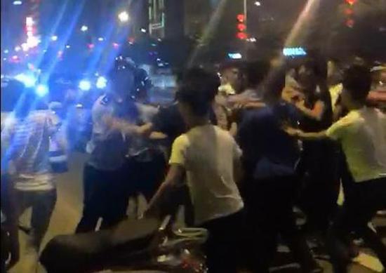 """现场视频显示,涉恶团伙先后出动了数十名""""马仔""""到场,对廉江警方飞虎队员进行殴打,并涉嫌将警方所抓获的涉案疑犯抢走。截屏图"""