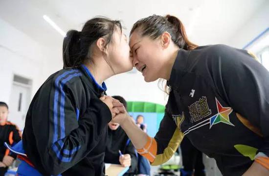 亲吻和拥抱是张杰对孩子们经常做的动作。图为张杰(右一)在鼓励小队员。(2017年5月12日摄)。新华社记者王凯摄