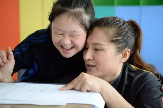 """2017年5月12日,张杰(右一)在绘画课上辅导队员""""大宝""""。新华社记者王凯摄"""