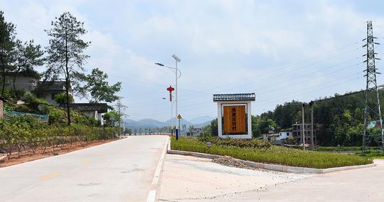 """崭新的古坊村,村口立着一块""""秀美古坊村""""的牌子。"""