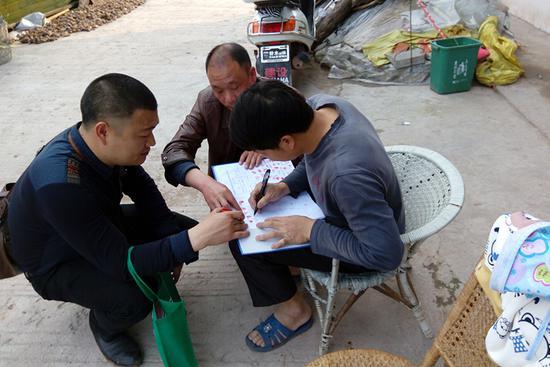 2016年3月,邹士荣(左)和李森源(中)在动员村民加入合作社。