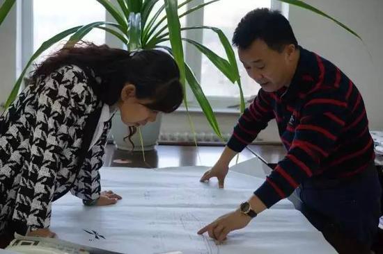 ▲ 于际方(右)和孙素娟在研究白狼镇规划图
