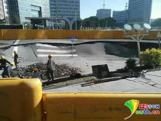 图为相关单位正在抢修,塌陷路段已被用挡板隔离开。
