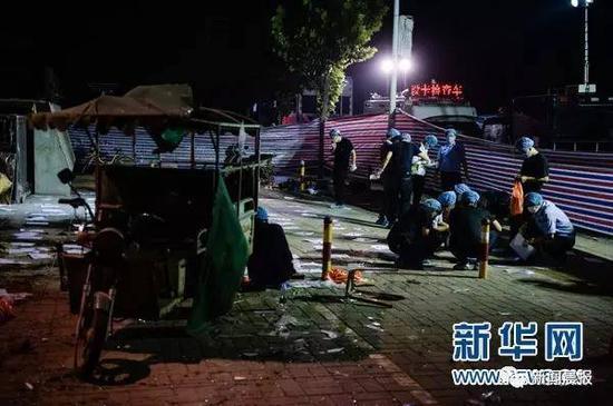 6月16日凌晨,法医等工作人员在江苏丰县创新幼儿园门前做清理、鉴定工作。来源/新华社