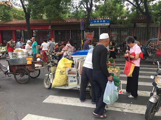 清晨6点王城公园门口,买菜的多是大爷大妈,8点钟摊铺全部收摊。