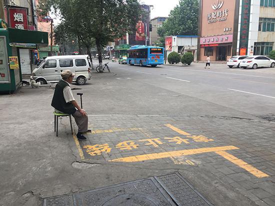 清晨6点洛阳街头,一位大爷坐在街边听收音机。