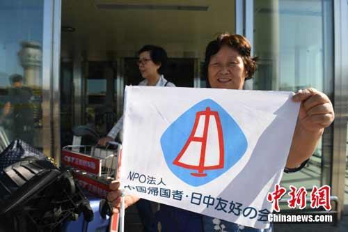 图为日本遗孤代表团成员展示中日友好标志。 王舒 摄