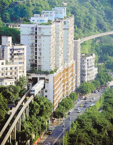 """在轻轨2号线李子坝站,轻轨列车""""穿""""居民楼而过。"""