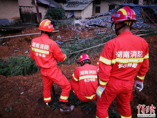 宁乡消防官兵担任对山体滑坡地位埋葬的屋宇停止搜救跟救济。拍照 李玺
